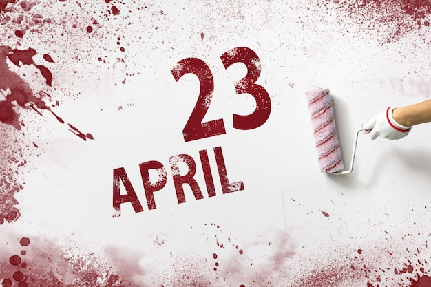 April 23rd. day 23 of month, calendar date. the hand holds a roller with red paint and writes a calendar date on a white background. spring month, day of the year concept.