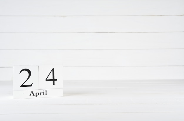 April 24th, day 24 of month, birthday, anniversary, wooden block calendar on white wooden background with copy space for text.