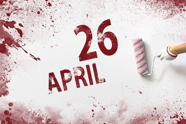 April 26th. day 26 of month, calendar date. the hand holds a roller with red paint and writes a calendar date on a white background. spring month, day of the year concept.