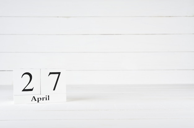 April 27th, day 27 of month, birthday, anniversary, wooden block calendar on white wooden background with copy space for text.