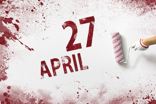 April 27th. day 27 of month, calendar date. the hand holds a roller with red paint and writes a calendar date on a white background. spring month, day of the year concept.
