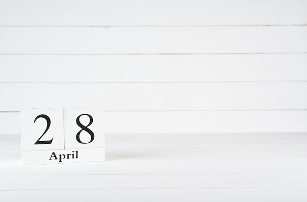 April 28th, day 28 of month, birthday, anniversary, wooden block calendar on white wooden background with copy space for text.