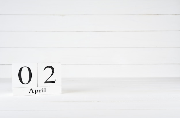 April 2nd, day 2 of month, birthday, anniversary, wooden block calendar on white wooden background with copy space for text.