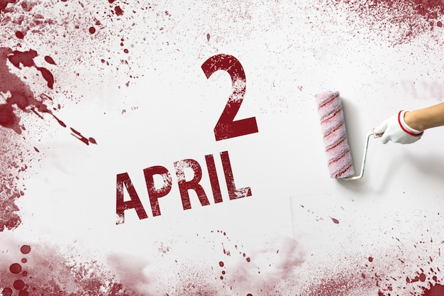 April 2nd. day 2 of month, calendar date. the hand holds a roller with red paint and writes a calendar date on a white background. spring month, day of the year concept.