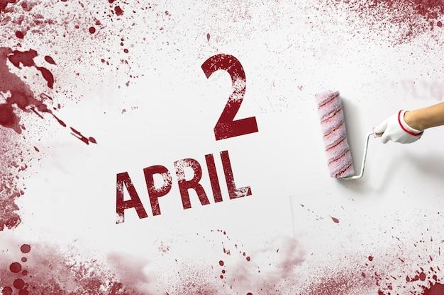 4월 2일 매월 2일, 달력 날짜. 손은 빨간색 페인트로 된 롤러를 잡고 흰색 배경에 달력 날짜를 씁니다. 봄 달, 올해 개념의 날.