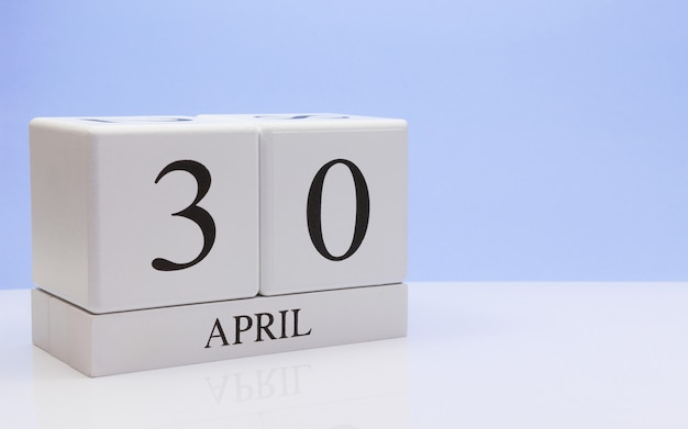 April 30st. day 30 of month, daily calendar on white table with reflection