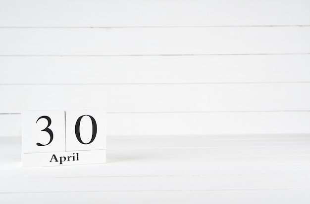 April 30th, day 30 of month, birthday, anniversary, wooden block calendar on white wooden background with copy space for text.