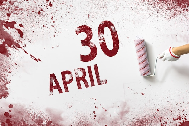 April 30th. day 30 of month, calendar date. the hand holds a roller with red paint and writes a calendar date on a white background. spring month, day of the year concept.