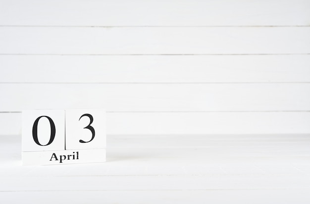 April 3rd, day 3 of month, birthday, anniversary, wooden block calendar on white wooden background with copy space for text.