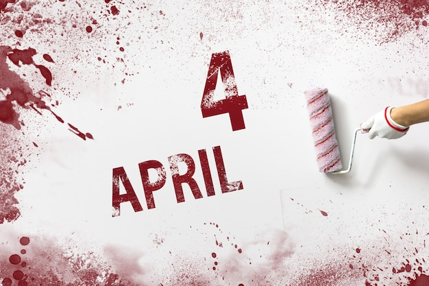 April 4th. day 4 of month, calendar date. the hand holds a roller with red paint and writes a calendar date on a white background. spring month, day of the year concept.
