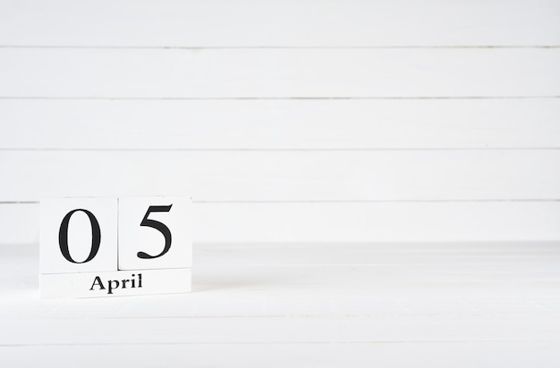 April 5th, day 5 of month, birthday, anniversary, wooden block calendar on white wooden background with copy space for text.