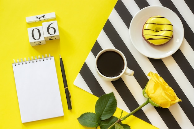April 6th. cup of coffee donut rose notepad on yellow background. concept stylish workplace