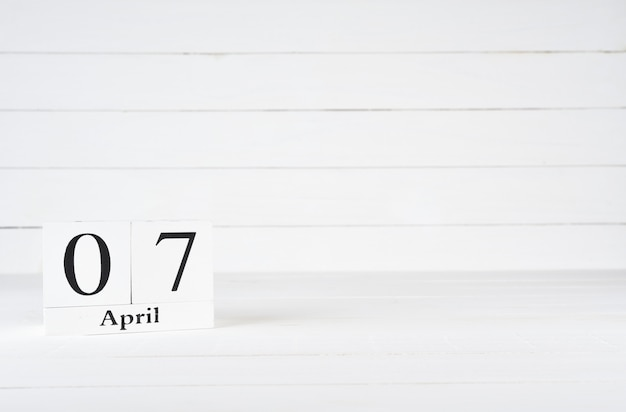 April 7th, day 7 of month, birthday, anniversary, wooden block calendar on white wooden background with copy space for text.