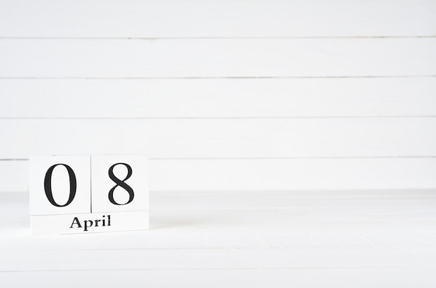 April 8th, day 8 of month, birthday, anniversary, wooden block calendar on white wooden background with copy space for text.