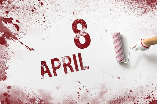 April 8th. day 8 of month, calendar date. the hand holds a roller with red paint and writes a calendar date on a white background. spring month, day of the year concept.