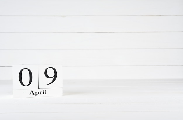 April 9th, day 9 of month, birthday, anniversary, wooden block calendar on white wooden background with copy space for text.