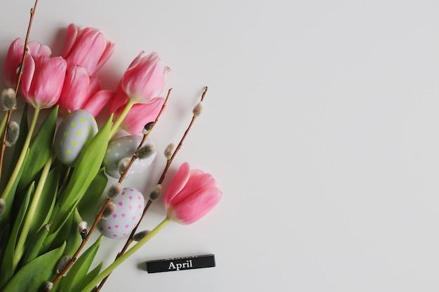 4月。ピンクのチューリップと卵とイースターの背景。春の休日のコンセプト。