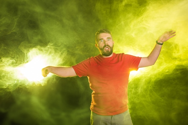 April fools day concept - evil crazy young man making funny faces on smoky background.