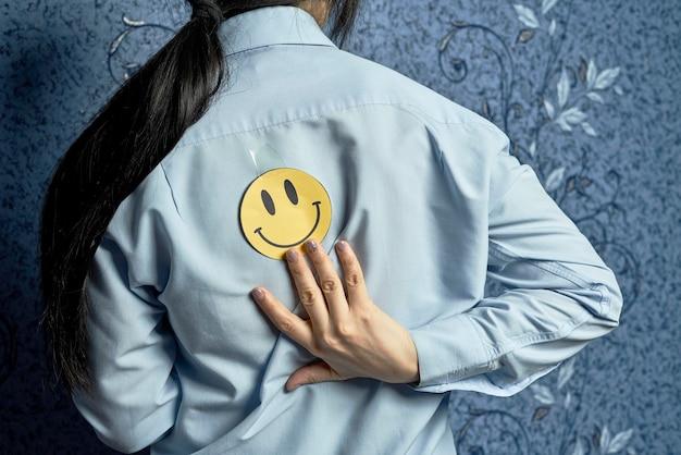 Первоапрельские шутки. наклейка с улыбкой на спине женщины. 1 апреля день дурака. забавный день. апрельская рыба
