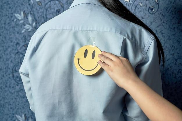 Первоапрельские шутки. сын кладет забавную наклейку на улыбающееся лицо на спину мам. забавный стикер на