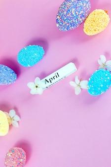 Апрельские надписи с пасхальными яйцами и весенними цветами на розовом фоне. вертикальный плоский.
