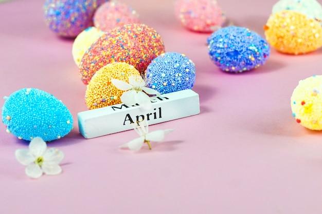 Апрельские надписи с пасхальными яйцами и весенними цветами на розовом фоне