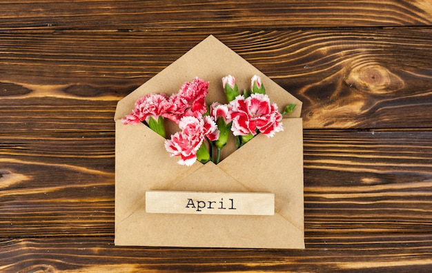 April text on envelope with red flowers on table