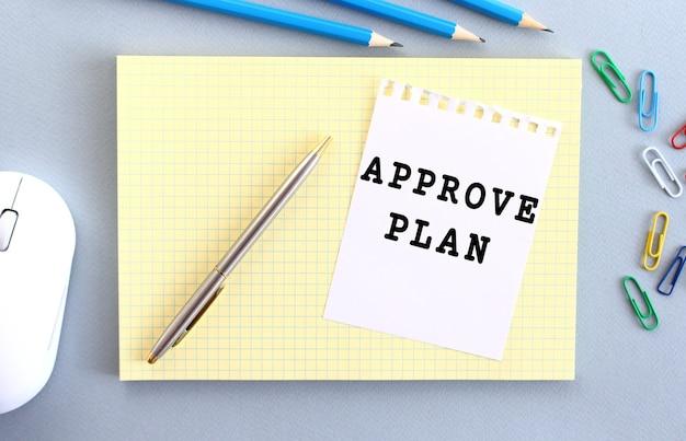Aprove plan은 사무용품 옆에있는 노트북 위에 놓인 종이에 적혀 있습니다.
