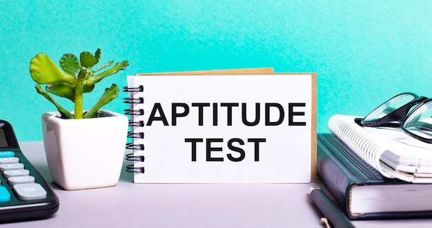 Aptitude test is written on a white card next to a potted flower, diaries and calculator. organizational concept