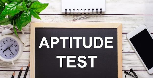 Тест на аптитуду написано на черной стене рядом с карандашами, смартфоном, белым блокнотом и зеленым растением в горшке