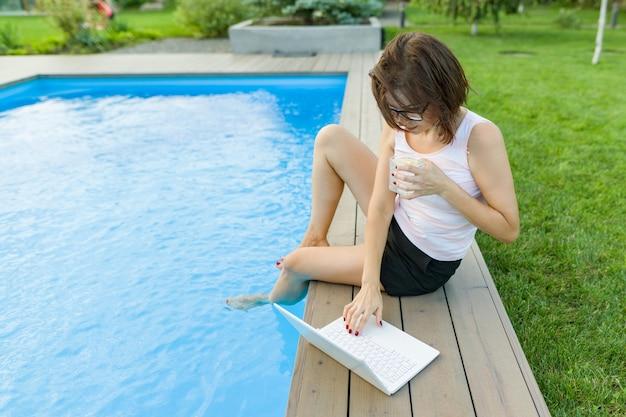 成熟した女性のフリーランサーはプールのそばに座ってaptopを使用します