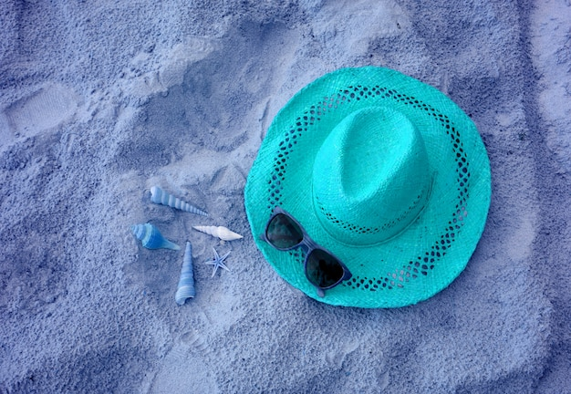 Aqua blue colored of straw hat with sunglasses and many little seashells on sandy beach