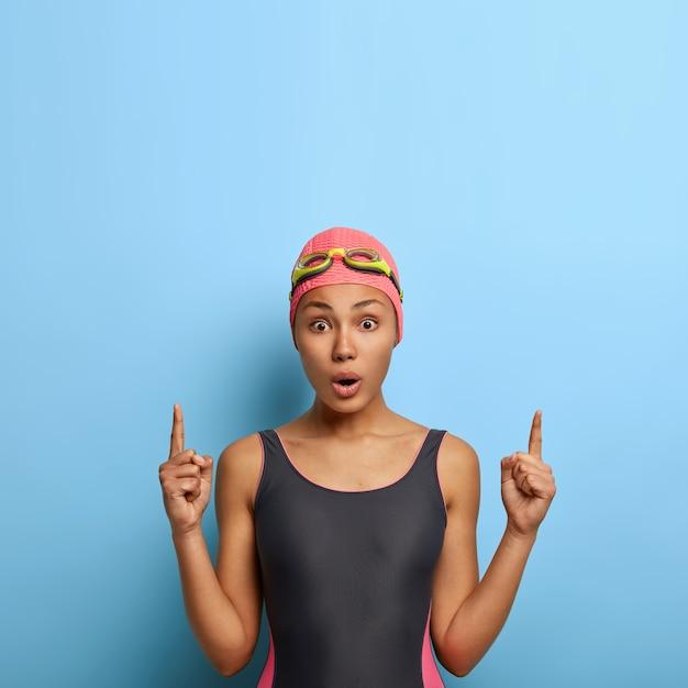 Концепция водного фитнеса. красивая спортивная плавательная девушка показывает выше с шокированным выражением лица