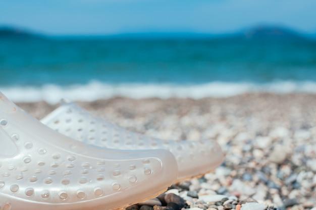 Aqua shoes on beach, vacation concept