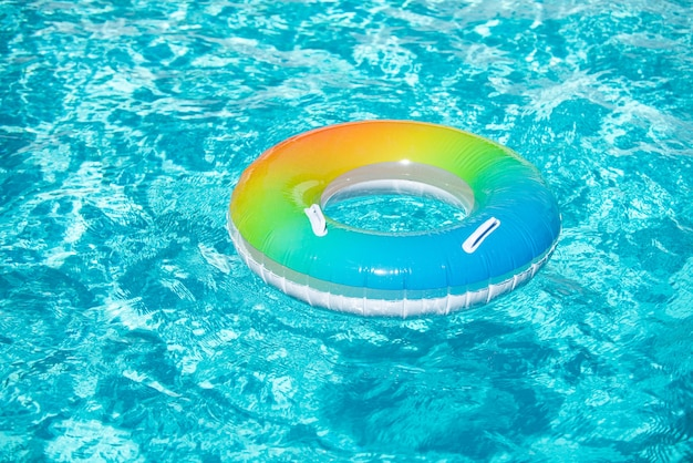 Aqua textured pool float ring floating in a refreshing blue swimming pool on summer background