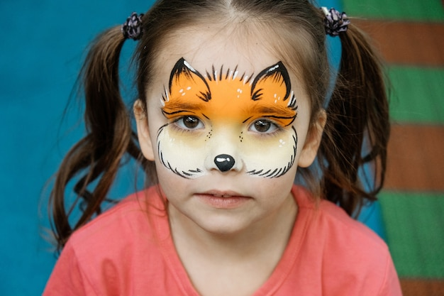 Aquagrim on the child's face. portrait of a girl with a chanterelle pattern on her face.