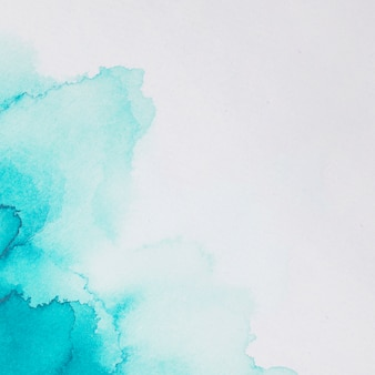 Aquamarine blots of paints on white paper