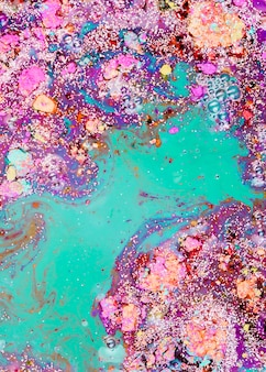 Aquamarine liquid blending with purple crumbs