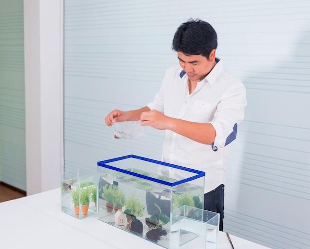 집에서 애완 동물과 취미를위한 수족관. 새로운 물고기와 함께 비닐 봉지를 들고.