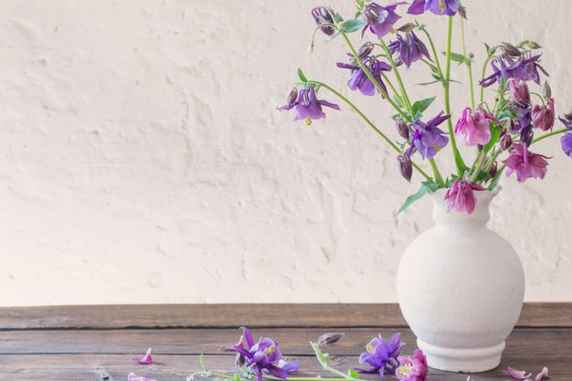Aquilegia flowers in white vase on wooden table
