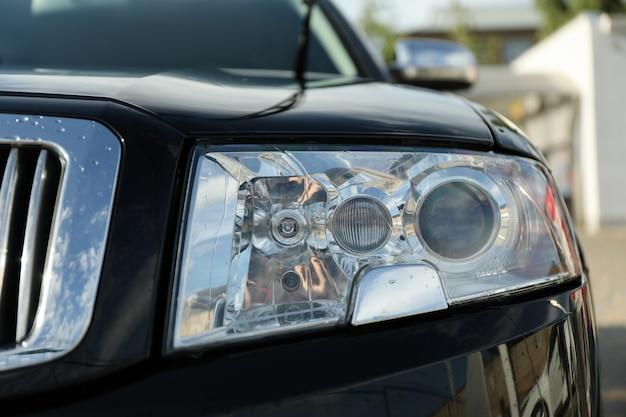 Прожектор фары черного седана, крупный план.
