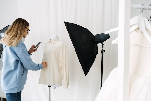 Ar vr technology in fashion industry female designer shotting clothes on mannequin by cell phone for