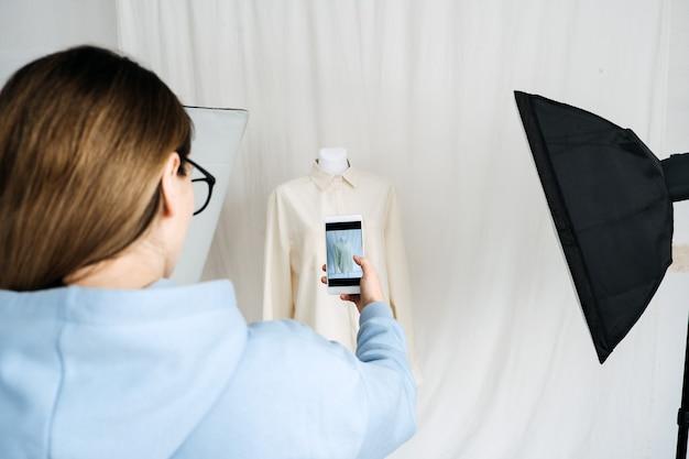 패션 산업의 ar vr 기술. 증강 현실 응용 프로그램을 위해 휴대 전화로 마네킹에 옷을 입히는 여성 디자이너. 패션 및 소매 분야의 ar vr 솔루션.