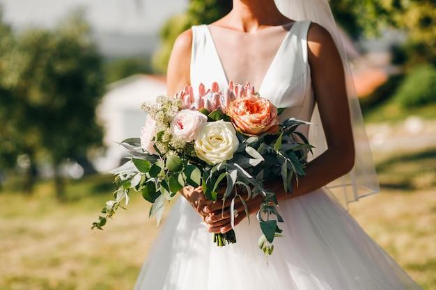 花嫁の散歩。古典的なドレスの美しい花嫁はarと歩く