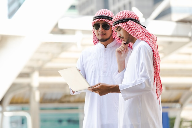 Arab business man call phone working on taplet in the city