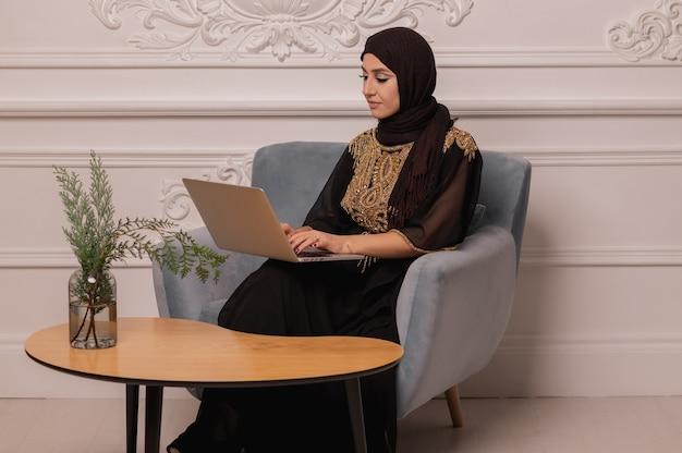自宅からラップトップに取り組んでいるアラブのビジネスウーマン。