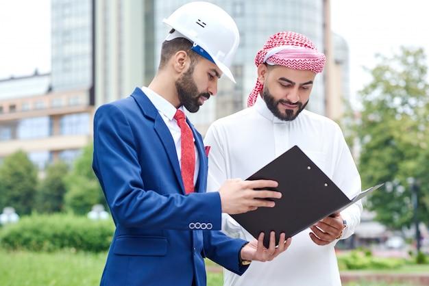 アラブのビジネスマンが彼の建築家との契約書類をチェック