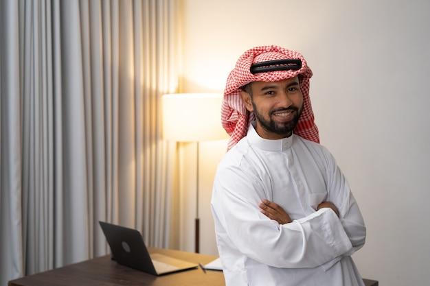 立っている間交差した手で笑ってターバンのアラブの実業家