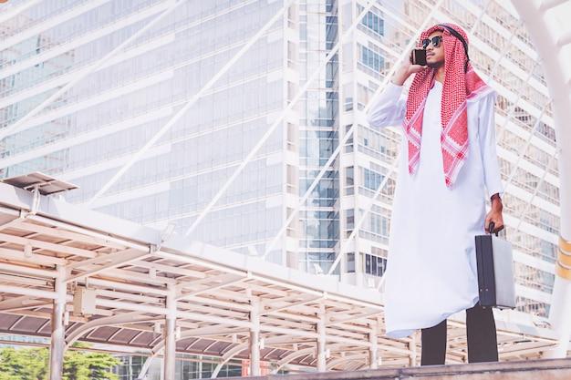 Обмен сообщениями арабского бизнесмена на мобильном телефоне в городе