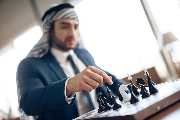Arab businessman playing chess at table at hotel room.